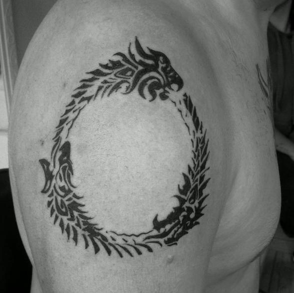 Кельтский стиль татуировки уроборос на плече